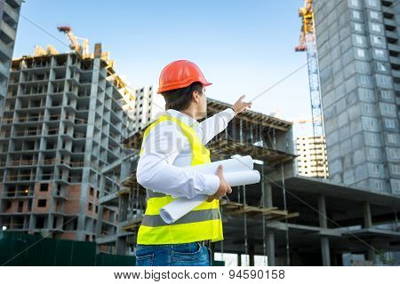Manager In Hardhat Pointing At Crane On Building Site