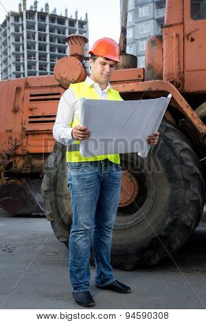 Engineer Reading Instruction To Bulldozer At Building Site