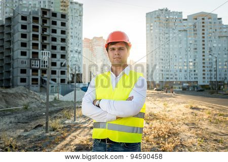 Engineer In Hardhat Posing Against Building Under Construction