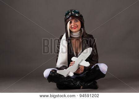 smiling woman in aviator hat sitting with toy airplane in hands