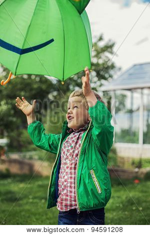 Adorable toddler boy play with green umbrella. Outdoors portrait