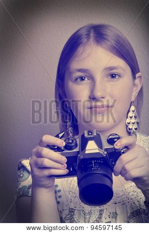 Instagram portrait of young girl teenager photographer holding vintage old camera shooting photographs