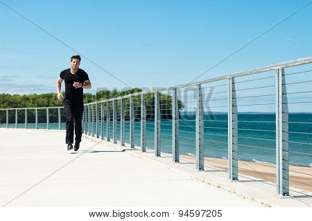 Man running or jogging at a beachside park.