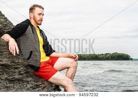 Young man sitting on a rocky cliff at a beach.