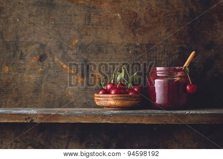 Jar of cherry jam and sour cherries on wooden shelf