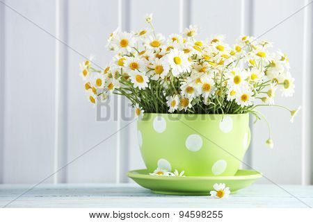 Beautiful bouquet of daisies in cup on wooden background