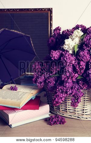 Beautiful lilac flowers in basket on floor in room close-up
