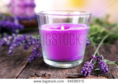Candles with lavender flowers on table close up