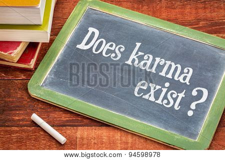 Does karma exist? A question in a white chalk  on a vintage blackboard with a stack of books against rustic wooden table