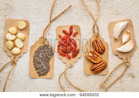 superfood abstract with price tags against barn wood (macadamia and pecan nuts, goji berries, chia seeds and garlic cloves) - healthy eating concept