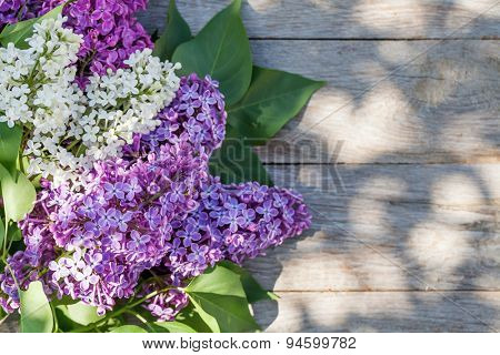 Colorful lilac flowers on garden table. Top view with copy space