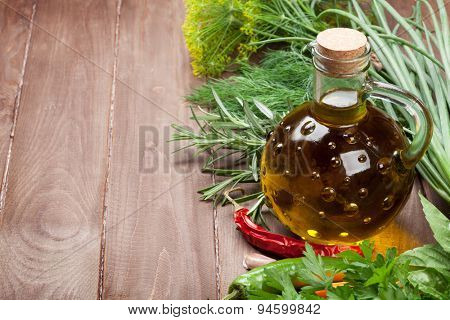 Fresh garden herbs and olive oil on wooden table. View with copy space