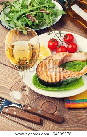 Grilled salmon and whtie wine on wooden table. Toned