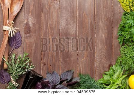 Fresh garden herbs over wooden table. Top view with copy space