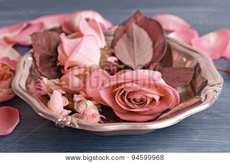 Beautiful pink roses in metal plate on wooden table, closeup