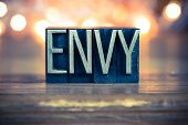 stock photo of envy  - The word ENVY written in vintage metal letterpress type on a soft backlit background - JPG