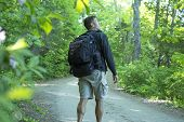 stock photo of dirt road  - Male Caucasian hiker with big backpack and muscular calves walks on dirt road while looking up into trees of beautiful green northeast forest of Maine - JPG