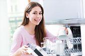 stock photo of dishwasher  - Woman loading dishwasher  - JPG