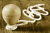 image of coil  - a traditional wooden spinning top with a string coiled in its axis on a rustic wooden surface - JPG