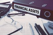 picture of asset  - Ring Binder with inscription Financial Assets on Background of Working Table with Office Supplies - JPG
