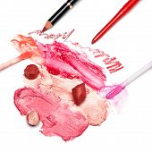 picture of lip  - Different colors of smeared and sliced lipstick lip gloss with brushes lip liners on white textured surface - JPG