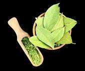stock photo of bay leaf  - Bay leaves in wooden bowl on black background - JPG