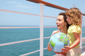 stock photo of cruise ship  - mother and daughter holding inflatable globe on cruise liner deck half body - JPG