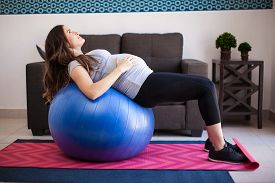 image of stability  - Profile view of a young pregnant woman stretching and supporting her back on a stability ball at home - JPG