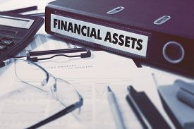 pic of asset  - Ring Binder with inscription Financial Assets on Background of Working Table with Office Supplies - JPG
