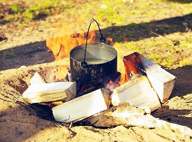 stock photo of smut  - sooty cauldron on campfire at forest - JPG
