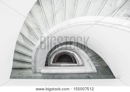 White grey spiral staircase with railing top view.