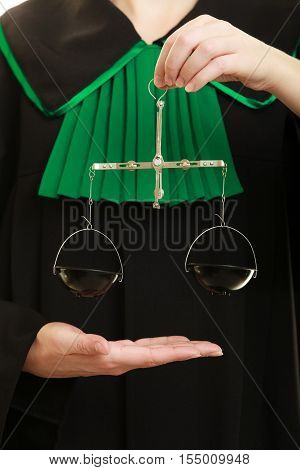 Law court concept. Woman lawyer attorney wearing classic polish black green gown holds scales. Femida - symbol sign of justice closeup