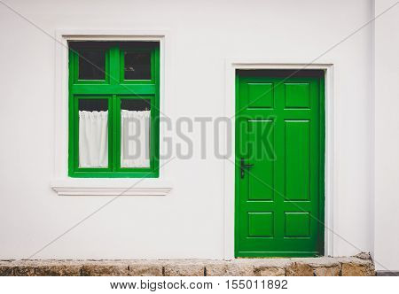 closed green door and window frame on white home