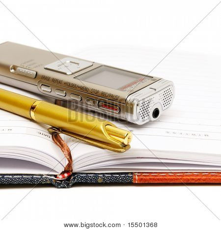 Dictaphone, notepad and ballpen on white background
