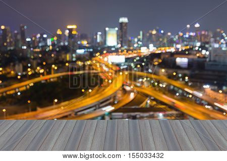 Opening wooden floor, Blurred lights overpass highway interchanged with city downtown background