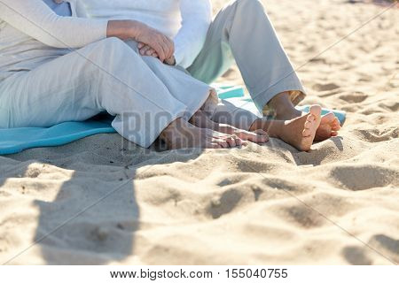 family, old age, travel, vacation and people concept - close up of happy senior couple sitting on plaid on summer beach
