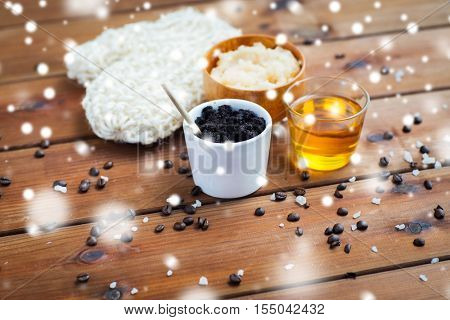 beauty, spa, bodycare, bath and natural cosmetics concept - homemade coffee scrub in cup with wisp and honey on wooden table over snow