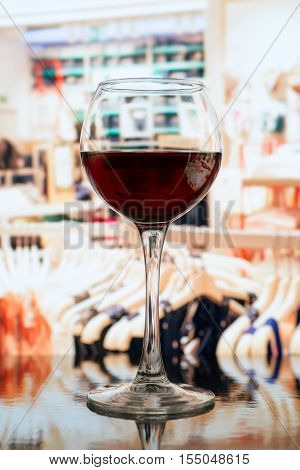 Wine glass against blurred clothes store background