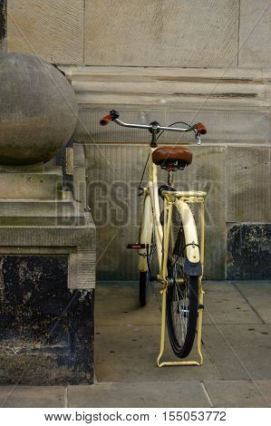 an old yellow bicycle. leather seat with shock absorbers and wheel