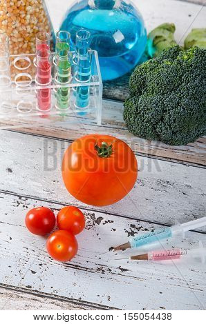 Syringe And Tomato. Genetically Modified Food Concept