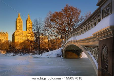 Cold Central Park winter sunrise on the frozen Lake with the Bow Bridge and Upper West Side buildings. Wintertime in Manhattan, New York City