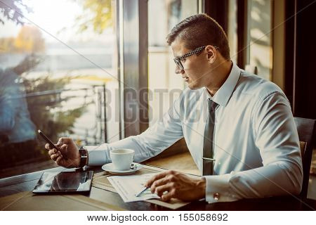 young successful businessman in a shirt and tie talking on the phone in a cafe for a cup of coffee looking schedules profit growth. Young man sitting in a cafe and looks charts and talking on the phone.