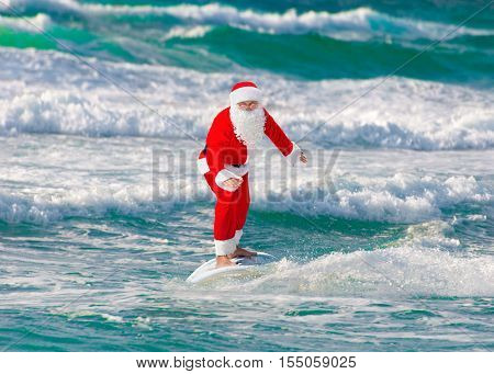 Santa Claus windsurfer go surfing with surfboard at ocean waves splashes in windy weather - New Year and Christmas active sports lifestyle concept