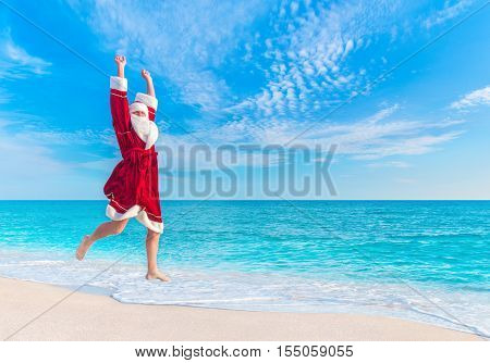 Santa Claus (Father Christmas) jump at sea sandy beach in the sky - New Year's vacation in hot countries concept