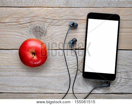 Smartphone with headphones and red apple on wooden table top view