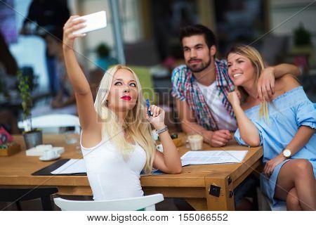 Three people having fun in cafe outdoors
