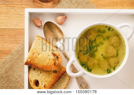 Hot broth with meatballs on wooden tray.