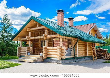 Traditional wooden house on green field in summer on the background of blue sky.