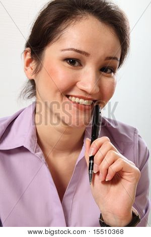 Beautiful Asian business woman holding pen