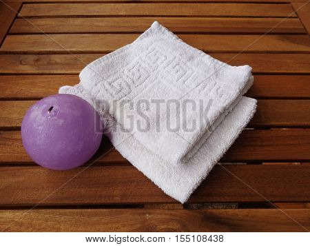 Set bath: Terry white towels and a round purple candle. All this on wooden boards